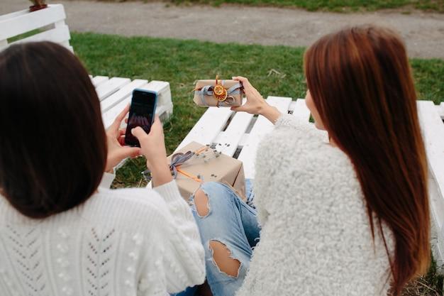 Twee vrouwen zitten buiten op een bank en schieten cadeautjes voor smartphone