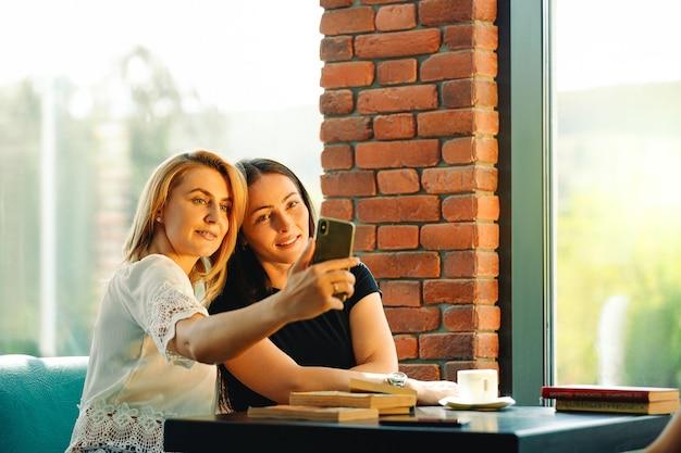 Twee vrouwen zitten in een restaurant kijken naar mobiele telefoon en glimlachen. vrienden zitten met koffie en boeken op tafel te kijken naar een mobiele telefoon. onderwijs en bedrijfsconcept.