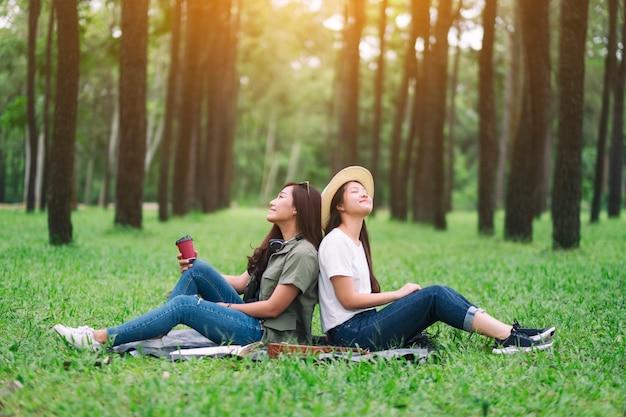 Twee vrouwen zitten in het bos met een ontspannen gevoel