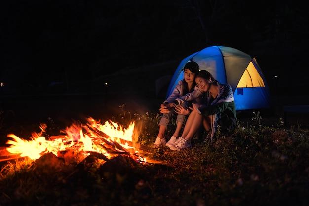 Twee vrouwen zitten rond een kampvuur en gewoon ontspannen