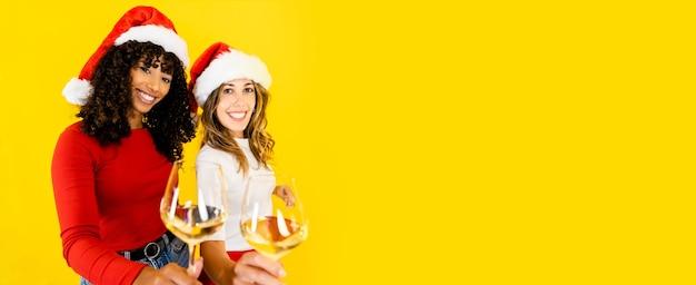 Twee vrouwen, zwarte hispanic en kaukasisch met kerstmuts, kijkend naar de camera met een glas witte wijn op grote gele kopie ruimte