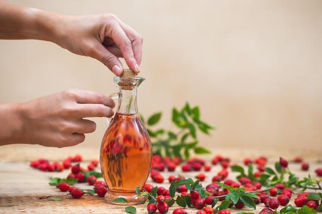 Twee vrouwenhanden sluiten glazen kolf met essentiële rozenbottelolie met kurken stop.