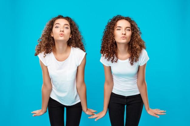 Twee vrouwentweelingen die kus verzenden, die over blauw stellen.