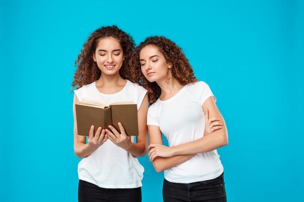 Twee vrouwentweelingen glimlachen, die boek over blauw lezen.