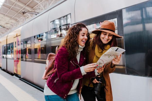 Twee vrouwenvrienden die bij station een trein wachten te reizen en te reizen. een kaart lezen en plezier maken.