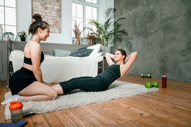 Twee vrouwenvrienden die thuis chatten, glimlachen en sporten maken