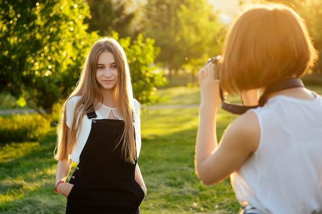 Twee vrouwenvrienden in het park die op een professionele camera fotograferen. fotoshoot fotosessie in de stad