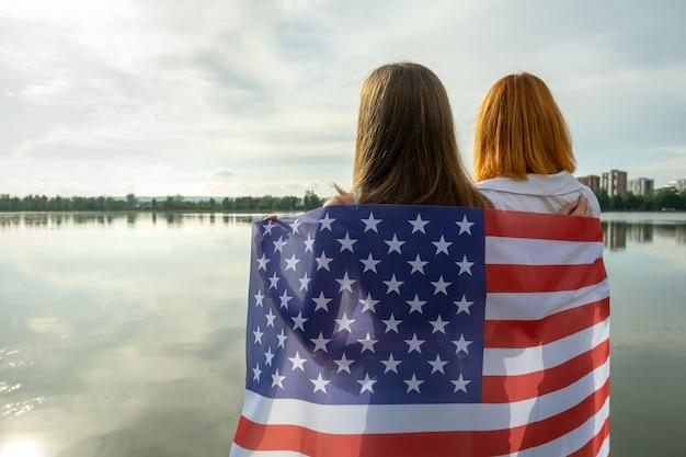 Twee vrouwenvrienden met de nationale vlag van de v.s. op hun schouders die samen staan