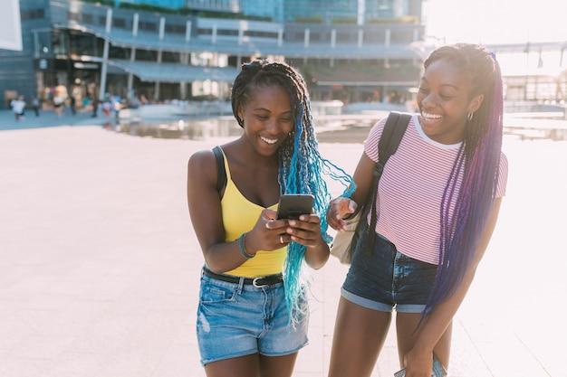 Twee vrouwenzusters openlucht gebruikend slimme telefoon die pret hebben