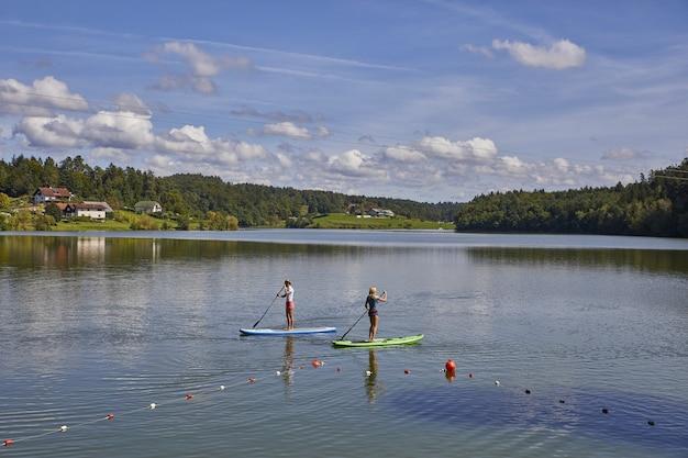 Twee vrouwtjes rijden op een stand-up paddleboard in het smartinsko-meer in slovenië
