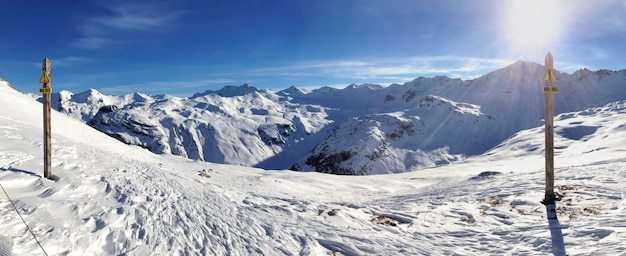 Twee waarschuwingsborden off-track die in het frans in sneeuwberglandschap schrijven onder zonnige blauwe hemel