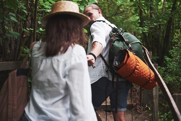 Twee wandelaars met rugzakken op de rug in de natuur.