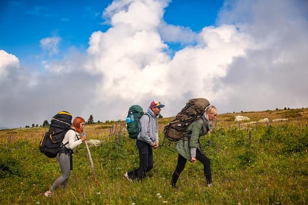Twee wandelende vrouwen en man met rugzak gaan langs het pad naar de bergen in een lange wandeling