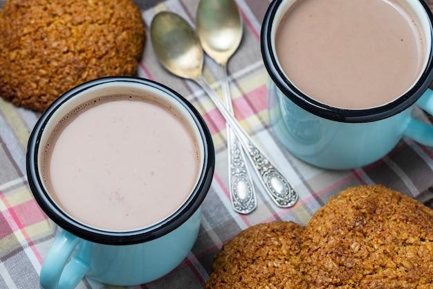 Twee warme chocolademelk en havermoutkoekjes op tafel. detailopname