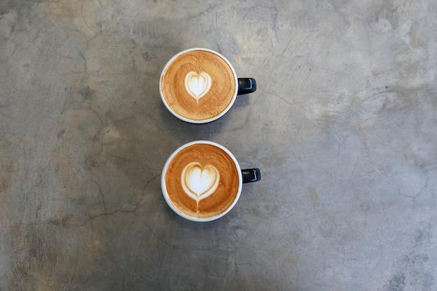 Twee warme kopjes cappuccino op concrete achtergrond valentijnsdag concept