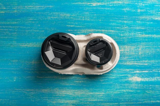 Twee wegwerp papieren bekers koffie en een wegwerp bekerhouder op een blauwe houten ondergrond