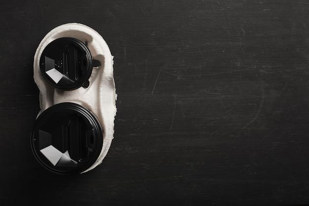 Twee wegwerp papieren bekers koffie en een wegwerp bekerhouder op een zwart hout