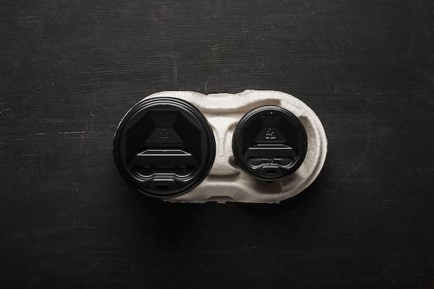 Twee wegwerp papieren bekers koffie en een wegwerp bekerhouder op een zwart houten oppervlak