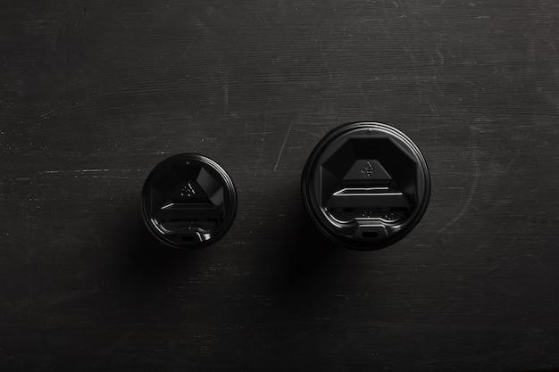 Twee wegwerp papieren bekers verschillende grootte koffie op een zwart houten oppervlak