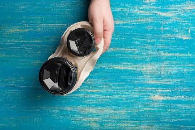 Twee wegwerp papieren kopjes koffie en een bekerhouder in een mannenhand op blauw