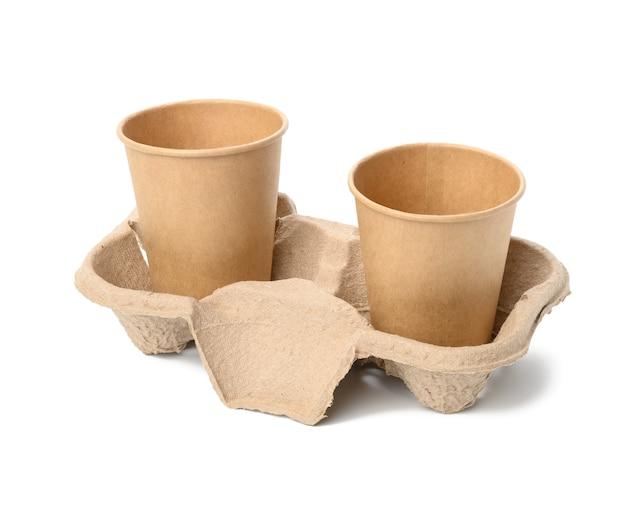 Twee wegwerpbekers van bruin papier staan in de lade, wit oppervlak, afhaalcontainers
