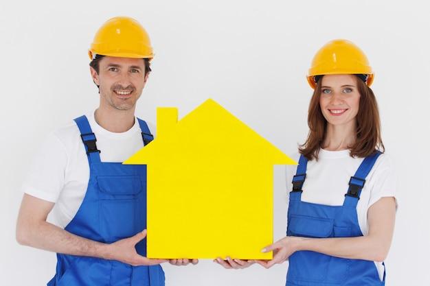 Twee werklieden die geel huissymbool houden