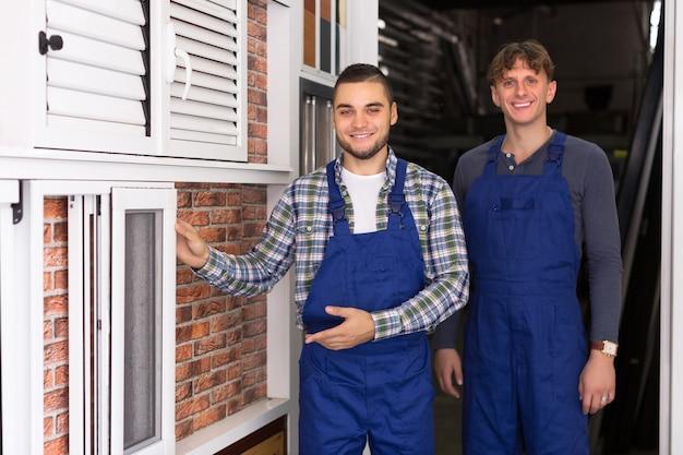 Twee werklieden die vensters inspecteren