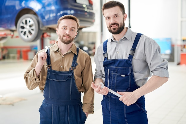 Twee werknemers poseren in car service shop