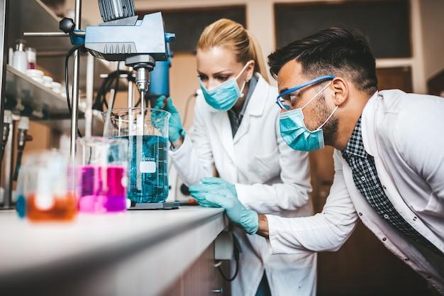 Twee wetenschappers en onderzoekers van middelbare leeftijd werken in een chemisch laboratorium.