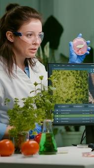 Twee wetenschappers praten over veganistisch vleesmonster die biotechnologische expertise op de computer typt. medisch team dat onderzoek doet naar vegetarisch voedsel dat genetisch is gemodificeerd in een chemisch laboratorium