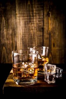Twee whisky shotglazen op donkere houten tafel, met ijsblokjes,