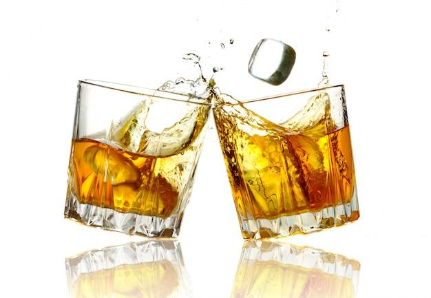 Twee whiskyglazen samen klinkend, geïsoleerd