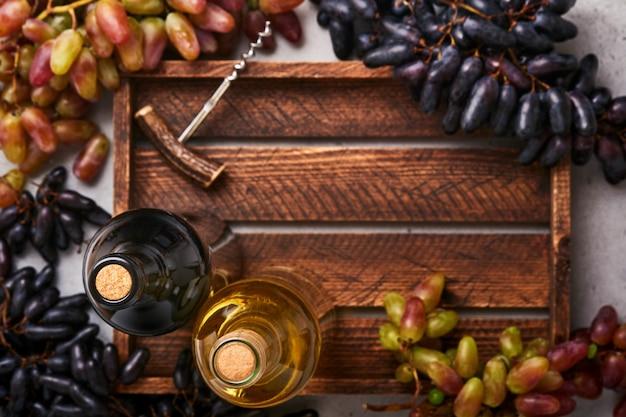 Twee wijnflessen met druiven en wijnglazen op oude grijze betonnen tafelachtergrond met kopieerruimte. rode wijn met een wijnstoktak. wijnsamenstelling op rustieke achtergrond. bespotten.