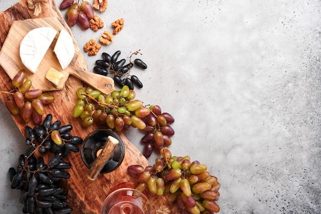 Twee wijnflessen met druiven, plak kaas camembert, noot en wijnglazen op oude grijze betonnen tafel achtergrond met kopieerruimte. rode wijn met wijnstoktak. wijnsamenstelling op rustieke stijl. bespotten.