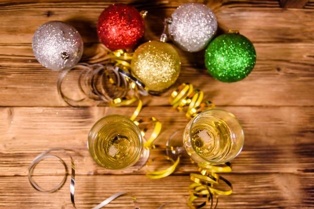 Twee wijnglazen met champagne en verschillende kerstversieringen op rustieke houten tafel. bovenaanzicht