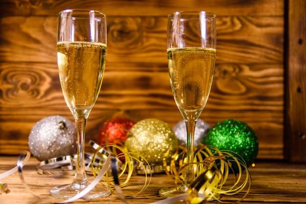 Twee wijnglazen met champagne en verschillende kerstversieringen op rustieke houten tafel