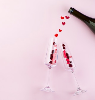 Twee wijnglazen met rode harten en fles. valentijnsdag concept