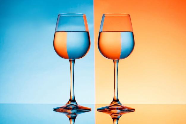 Twee wijnglazen met water over blauwe en oranje achtergrond.