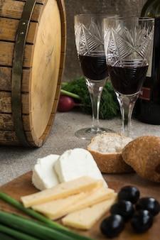Twee wijnglazen, olijven, kaas en brood staan op plundering