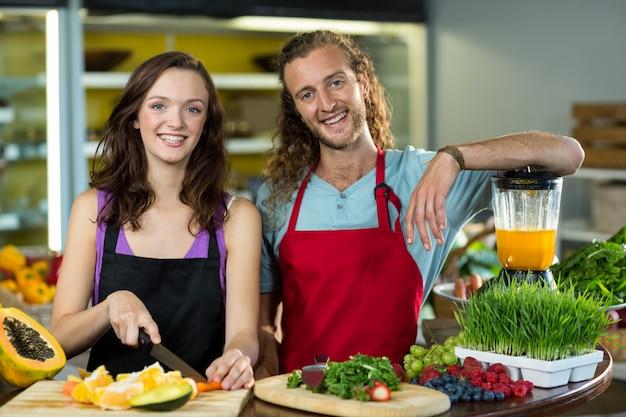 Twee winkelbediende hakken fruit aan de balie in gezondheid kruidenierswinkel
