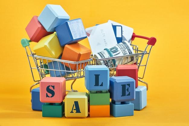 Twee winkelwagentjes met veelkleurige blokjes, creditcards en dollars op gele achtergrond