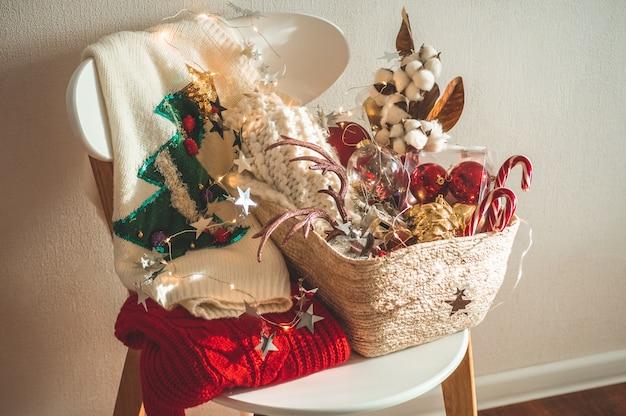Twee winterse truien op een stoel met een mand met kerstversieringen.