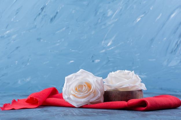 Twee wit roze bloemen op rood tafelkleed.
