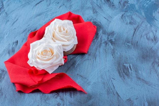 Twee witroze bloemen op rood tafelkleed op blauw.