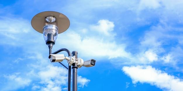 Twee witte bewakingscamera's op de de lantaarnpaalpost van de metaalstraatlantaarn openlucht op blauwe hemel