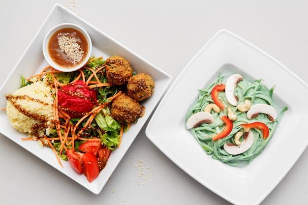 Twee witte borden met groene spinaziepasta, champignons, groenten en falafels op een witte achtergrond