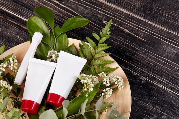 Twee witte cosmetische buizen met rode doppen en roller voor gezicht op boeket bloemen