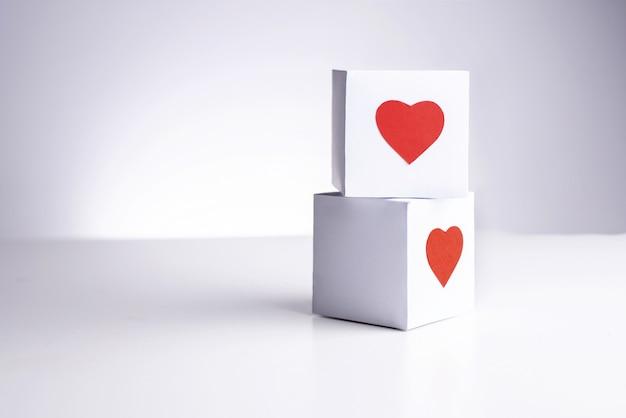 Twee witte dozen met rode harten op elkaar.