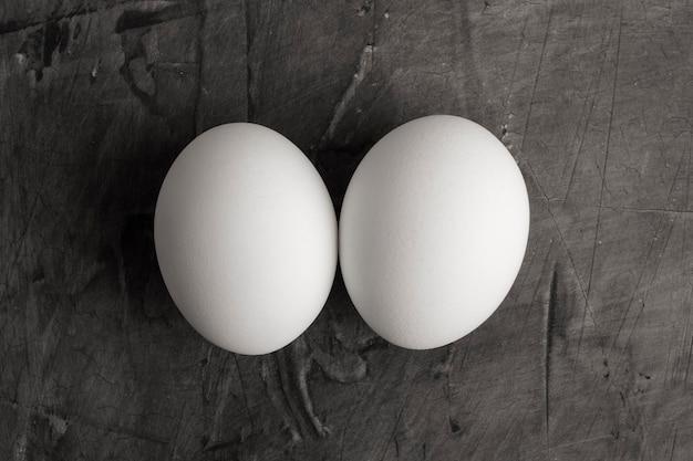 Twee witte eieren op een zwarte achtergrond. kopieer ruimte