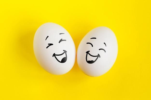 Twee witte eieren op geel concept als achtergrond. emoties lachen en geluk.